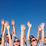Enthusiastic People with Arms Raised