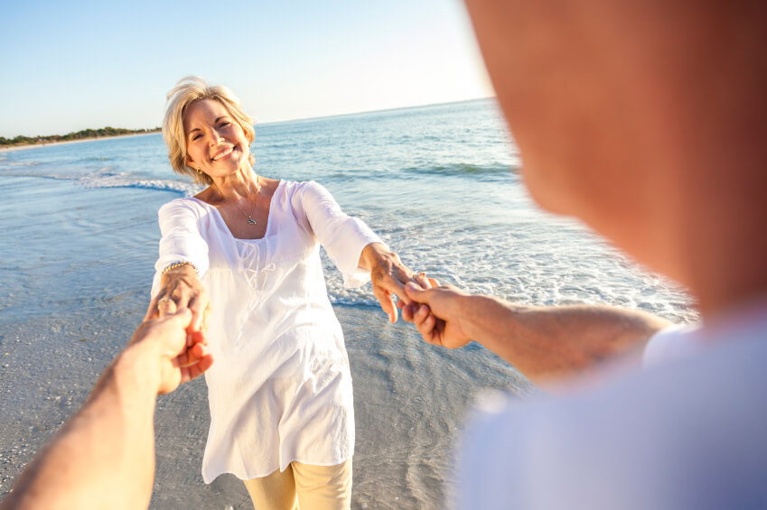 retired couple at the beach holding hands and smiling